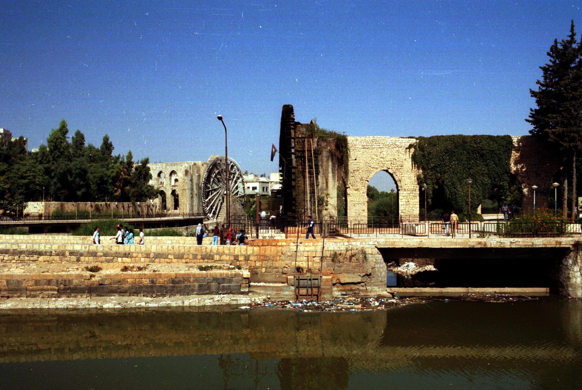 حماة 1985- ناعورة الجسرية وخلفها ناعورة المأمورية ثاني أكبر ناعورة في المدينة